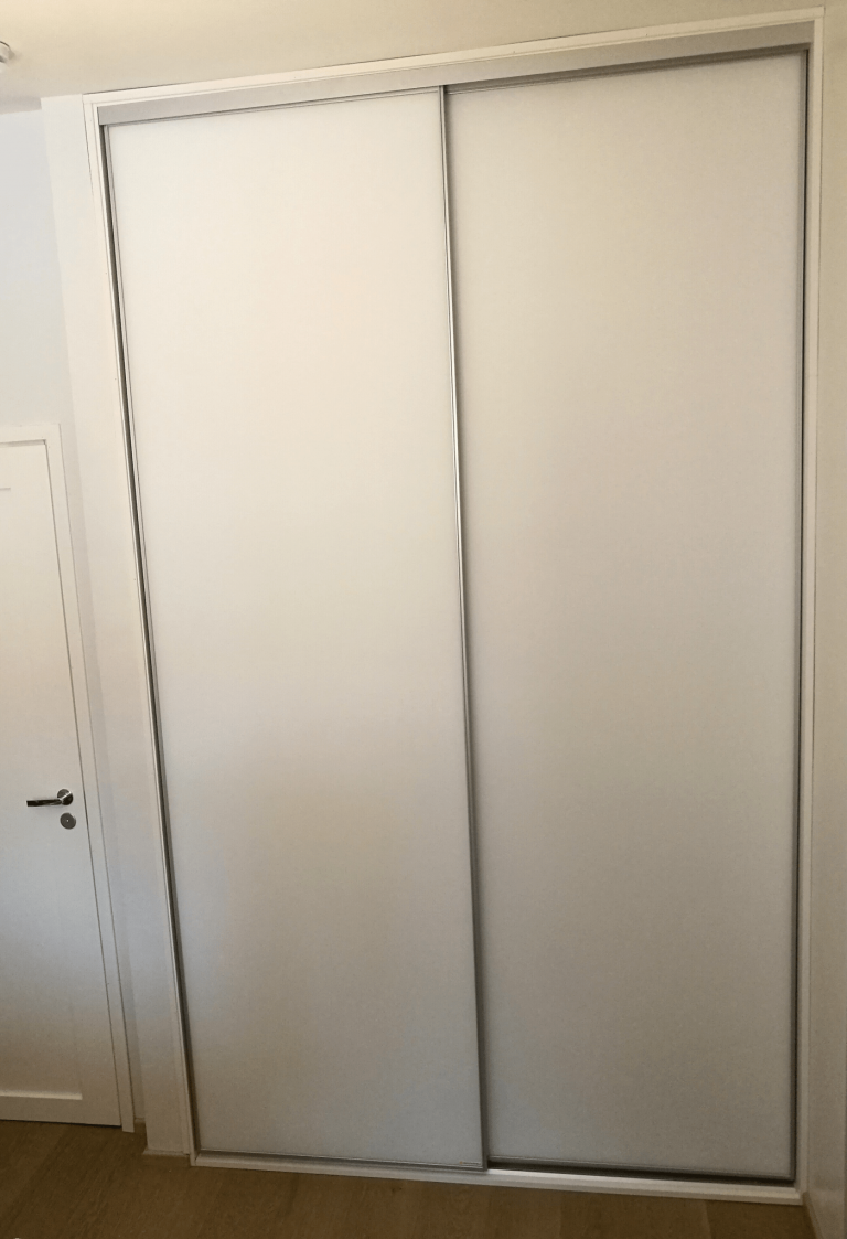 Valkoinen liukuovikaapisto mattavalkoisilla ovilla
